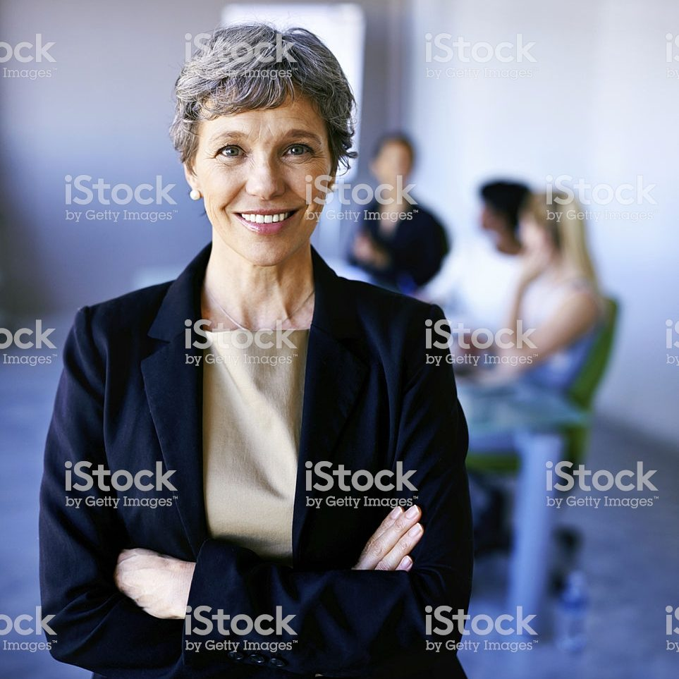 Portrait of a businesswoman standing in front of her colleagues during a meeting
