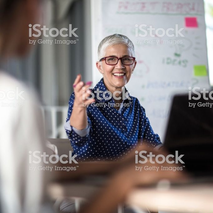 Happy mature businesswoman talking to her colleague during business meeting in the office.